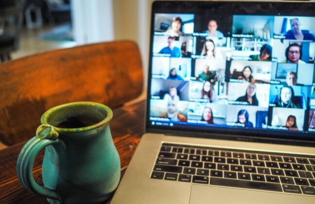 Virtual meeting on laptop next to coffee cup