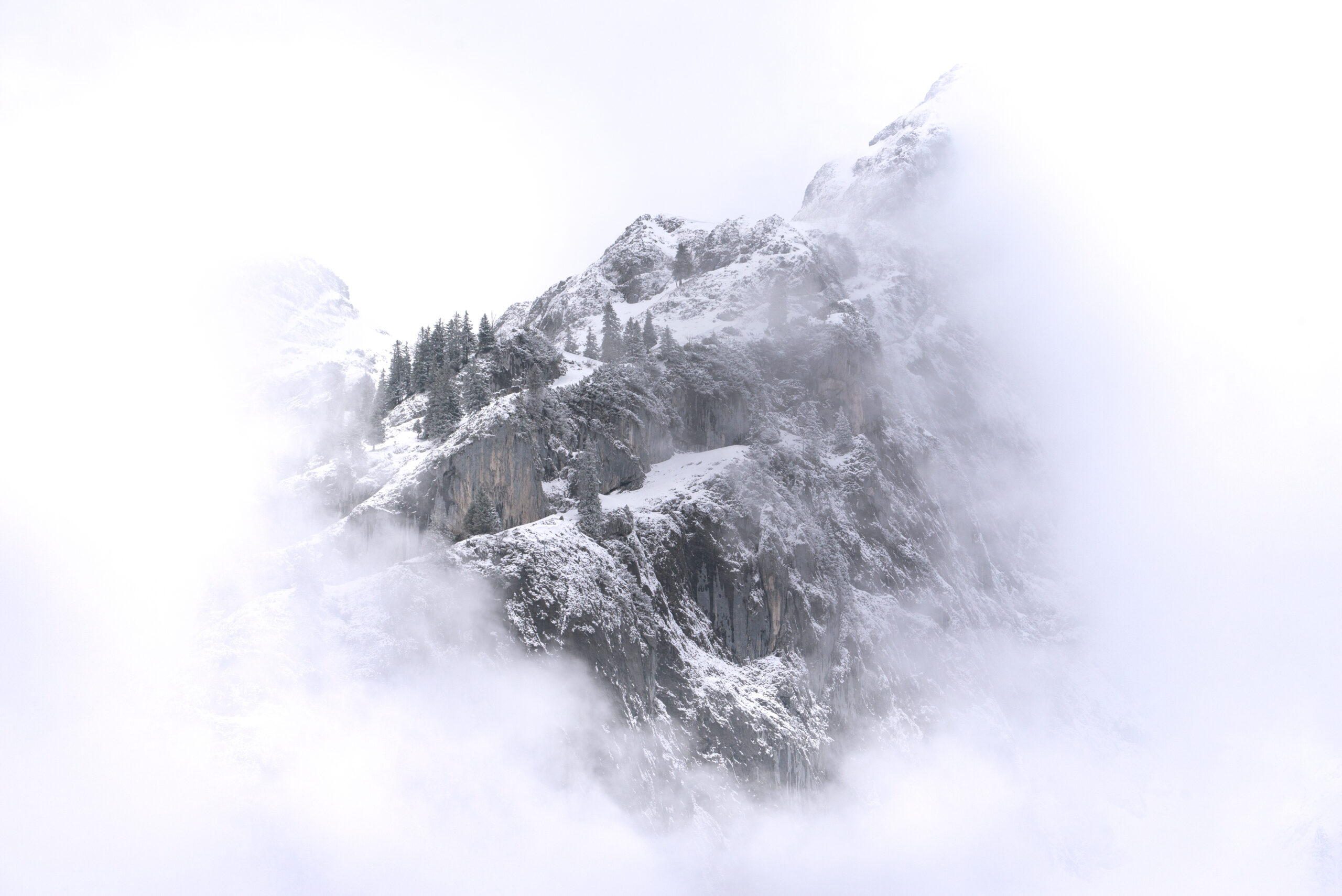 Close up of snowy mountain peak in fog
